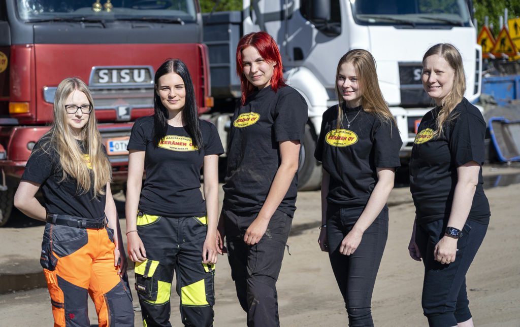 Viisi nuorta naista seisoo rivissä kuorma-autojen edessä. Jokaisella naisella on musta t-paita päällään, jossa on keltainen soikea alue, jossa lukeen Maanrakennus Keränen Oy.