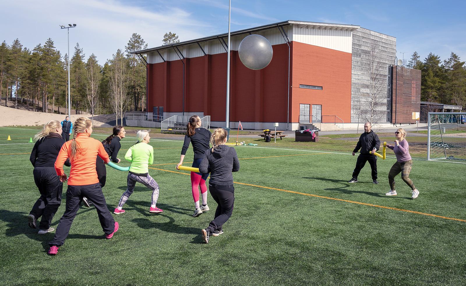 Henkilöt pelaavat palloa tekonurmikentällä auringonpaisteessa. Takana näkyy liikuntahalli ja mäntymetsä.
